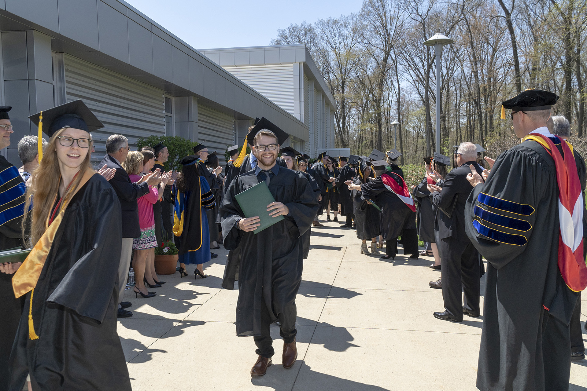 A student walking down the graduation gauntlet