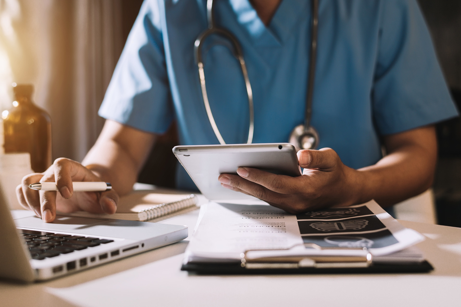Health professional entering data into a laptop