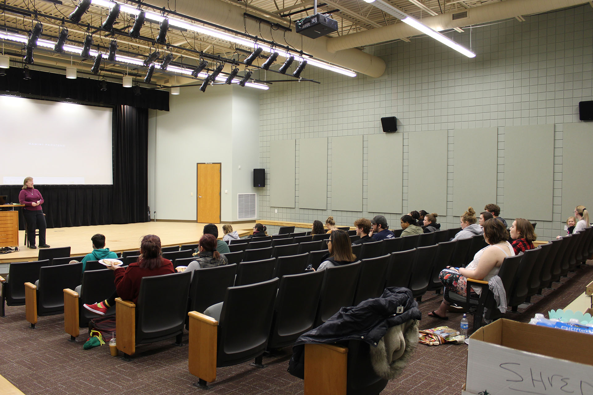 Students sitting in the Student Activity Center Events Theatre listening to a spreaker