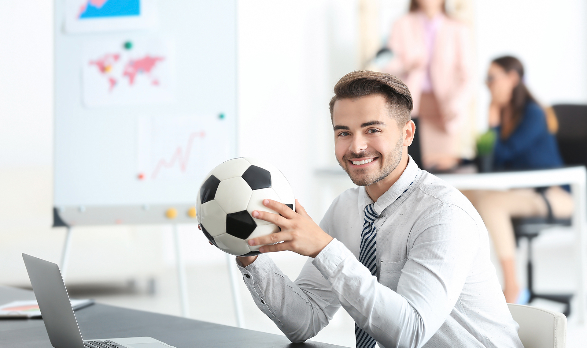 Man at desk holding a soccer ball