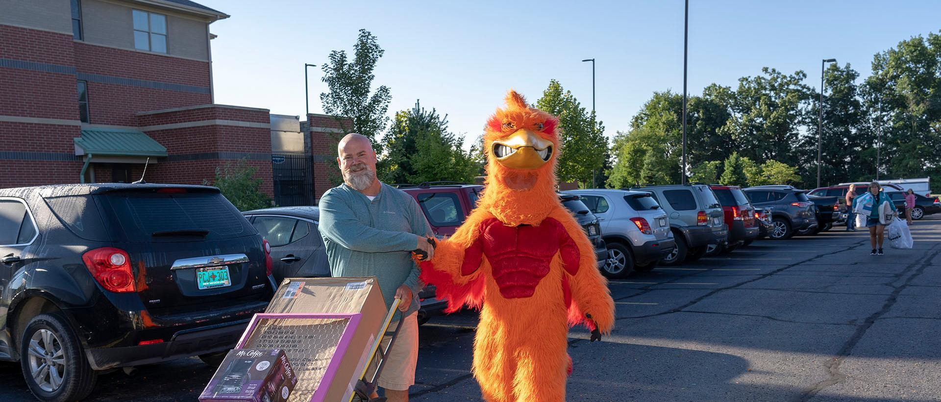 A parent shaking hands with the roadrunner mascot