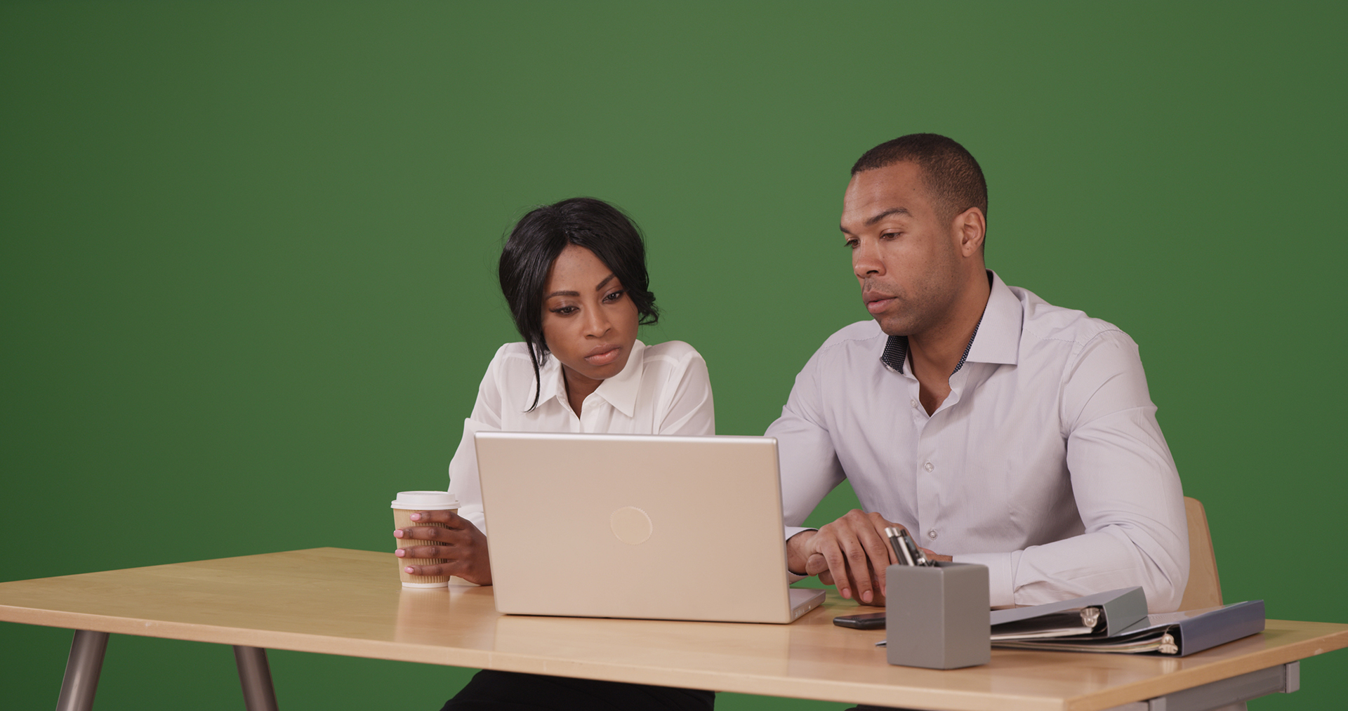 A man and woman looking at a computer